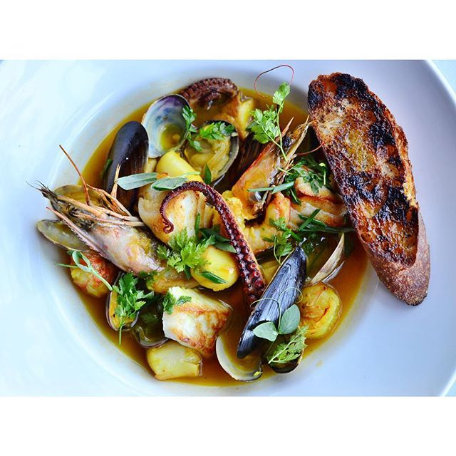 Meet our July Tuesday Night Supper - Brodino Misto di Pesce.  To prepare this dish, Chef Balesteri soaks snapper bones overnight to remove any overpowering fish flavor. The next morning he drains the water, adds fresh water, and boils it to create a basic fish stock before adding shells from shrimp, lobster and any other shellfish on hand. He adds white wine, saffron, and fennel pollen then pours the broth over head on prawns, halibut, rock shrimp, mussels, clams and octopus. The final…