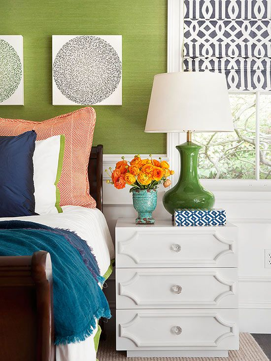The trellis design of the roman shades in this inviting, colorful bedroom is a classic pattern that add a ton of personality.