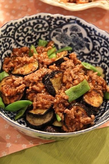 秋茄子とインゲンのそぼろあんかけ 作り方はね、フライパンに茄子(2本)・モロッコインゲン(8本)を入れ、火にかけ、表面の水分を飛ばすように炒めたら、油(大さじ2)を加えて茄子に油を吸わせるように揚げ焼きし、焼けたらいったん皿に取り出す。同じフライパンに豚ひき肉(150g)を入れて炒めたら、水(150㏄)・醤油(大さじ2)・酒とみりん(大さじ1)・砂糖(大さじ1.5)・鰹だしの素(小さじ1/4)で煮立て、最後に水溶き片栗粉(小さじ2+水小さじ2)でとろみをつけて茄子とインゲンにかける。