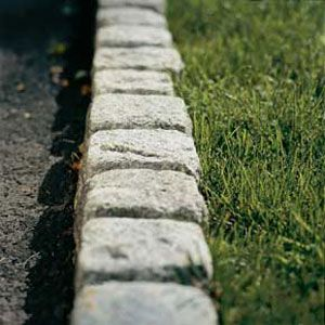 Granite or stone setts edging a drive or path - however you need to think about mowing up to these blocks which really should be laid at a lower level than the grass but higher than the hard surface.