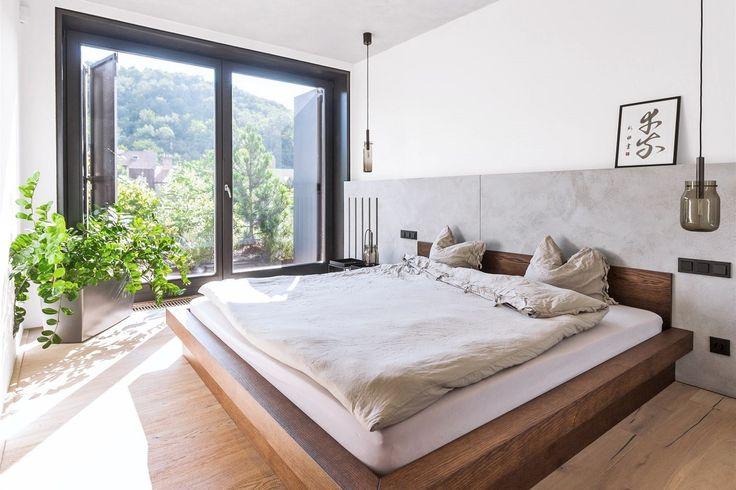 Jednoduchá ložnice zcela kopíruje charakteristické rysy celé realizace – převládá dřevo, beton a velké bílé plochy. Dovoluje tak vyniknout působivému výhledu do zeleně.