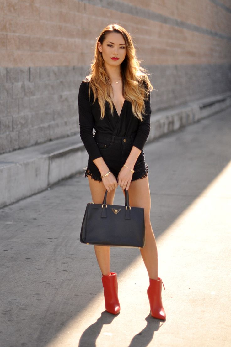 Make a black long sleeve blouse and black denim shorts your outfit choice to create a chic, glamorous look. For the maximum chicness rock a pair of red leather booties.   Shop this look on Lookastic: https://lookastic.com/women/looks/black-long-sleeve-blouse-black-shorts-red-ankle-boots/14697   — Black Long Sleeve Blouse  — Black Denim Shorts  — Black Leather Tote Bag  — Red Leather Ankle Boots