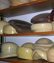 Das Bild zeigt verschiedene hölzerne Hutformen in einem Regal.