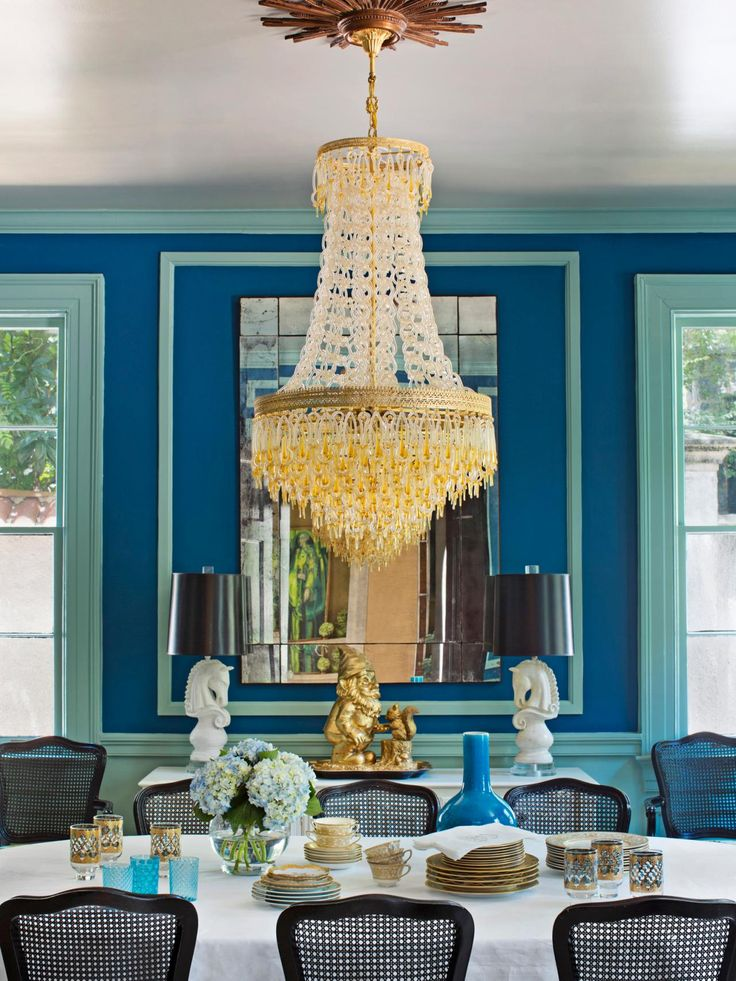 A Mediterranean Blue Wall With Robins Egg Trim Work Pairs Well Black Chairs In This Dramatic Dining Room An Ornate Chandelier Adds Elegance To