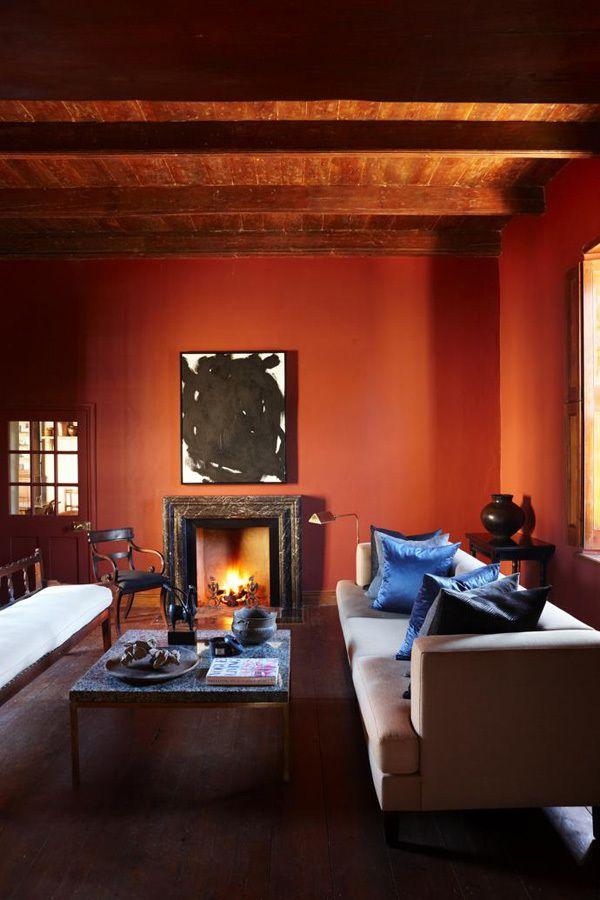 В гостиной красные стены. На окнах деревянные ставни защищающие комнаты от жары летом, а камин согревает зимой. .