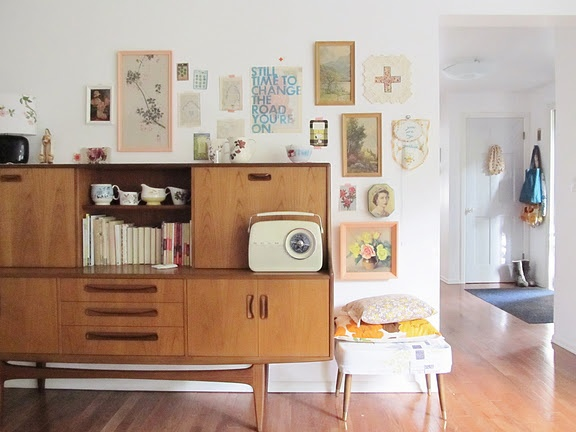 love all the photographs and picture frames.. not to mention the awesome piece of furniture.