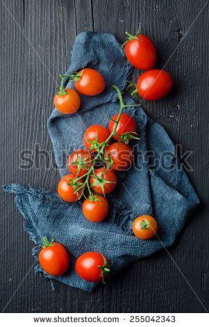 Cherry tomatoes over blue cloth, above view