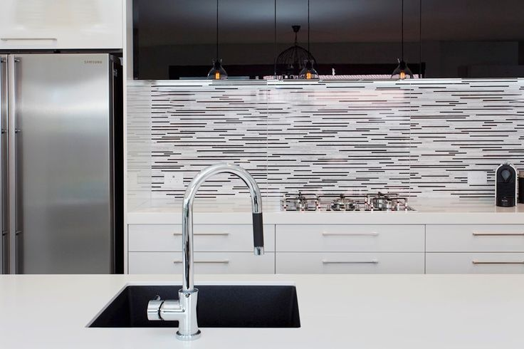 Detailed black and white tiles contrast the simplicity of the white kitchen