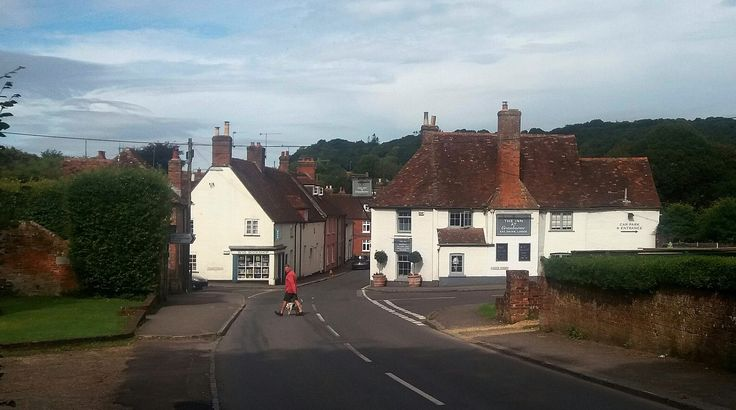 "https://flic.kr/p/M65AgD | Cranborne Dorset | Cranborne in Dorset. The village dates from Saxon times and was recorded in the Domesday Book of 1086 as Creneburne, meaning stream (bourne) of cranes. In this street view we see a man walking his dog, and the C16 ""New Inn"" and on the opposite side is the WVS  ""Book Shop"" The Driveway in the bottom left foreground is the entrance to Cranborne Manor."
