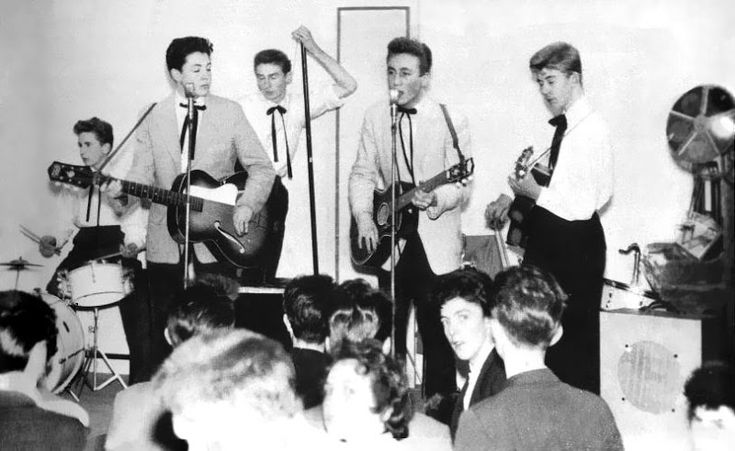 The Quarry Men band are pictured above. From left to right we see Colin Hanton on drums, Paul McCartney on guitar, Len Garry on tea chest bass, John Lennon on guitar, and Eric Griffiths on guitar. Photo taken by Leslie Kearney on November 23, 1957 in The New Clubmoor Hall on Broadway in Liverpool.