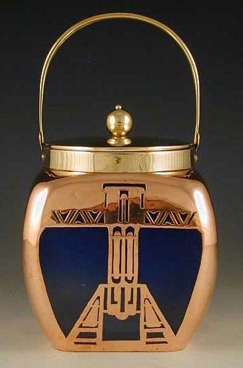 Loetz  Designer  DescriptionSatinised loetz biscuit barrel with secessioist copper overlay, lid & handle  Country of ManufactureAustria  Datec.1902