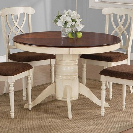 Pedestal dining table in buttermilk with a dark cherry-finished surface.    Product: Dining tableConstruction Materia...