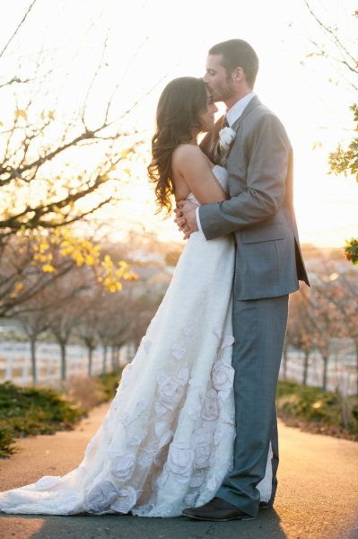 kiss on the forehead and sunlight coming through, and pose of the bride and groom