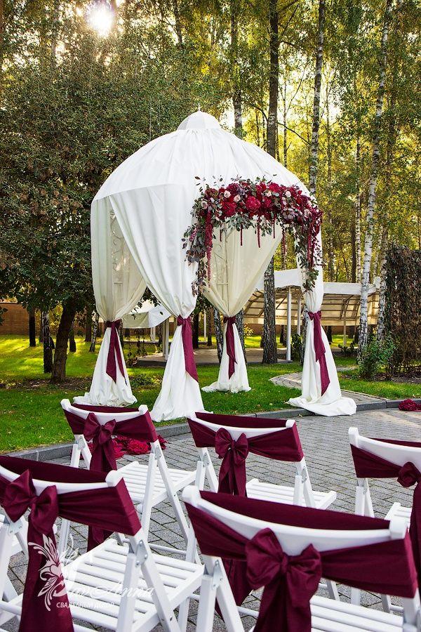 Яркое оформлениеосенней свадьбы в цвете Марсала в ресторане XO Exclusive Свадьба в модномцвете этогосезона также пополнила и наше портфолио, и мы рады, что это произошлоименно осенью. Благородный цвет в разгар Золотой теплой осени. Лучше не придумаешь! Красивая альтанка в ткани, оформленная насыщенной цветочной композицией, яркие ленты на стульях, и резная виньетка с помпонами вместо дорожки - церемония получилось очень сочной, даже с легкой дерзинкой, которую дает именно Марсала.