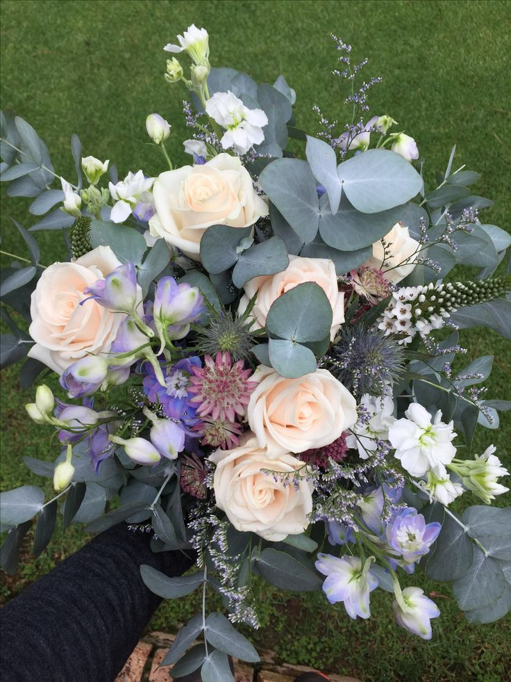 A brides beautiful loose, organic hand tied bouquet with lots of different purple hues. Designed by Bliss Floral Creations