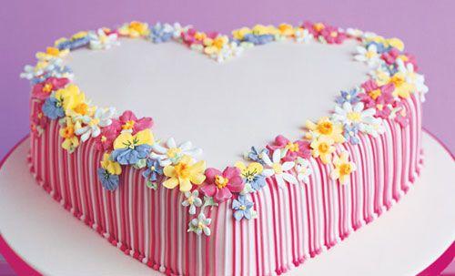 Torta per la festa della mamma a forma di cuore e decorata con fiorellini multicolore