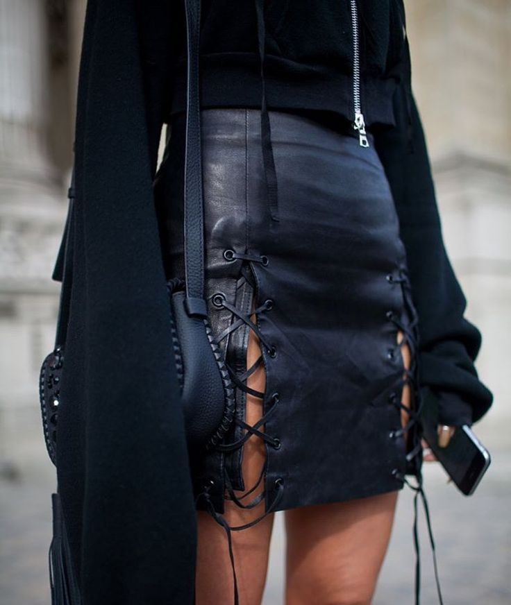 Leather lace-up mini skirt, black sweater with bell sleeves, and mini saddle bag.