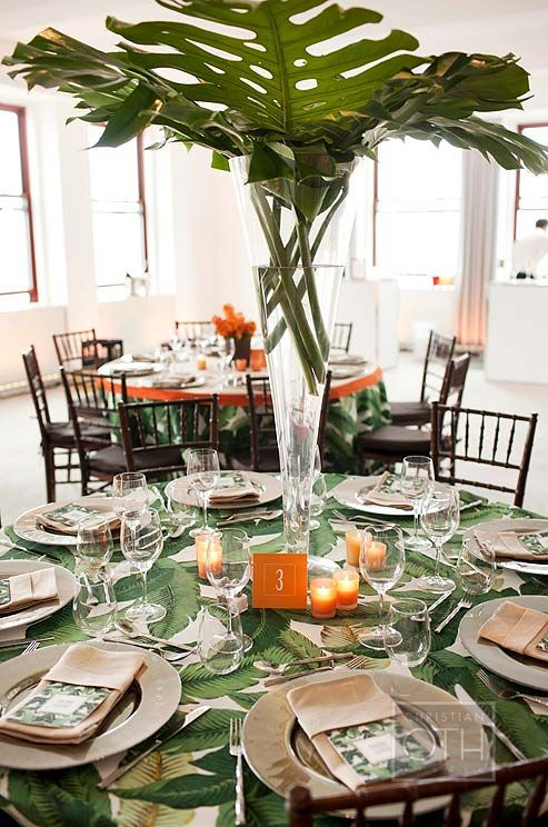 Clusters Of Orange Votive Candles Surround A Tall Vase