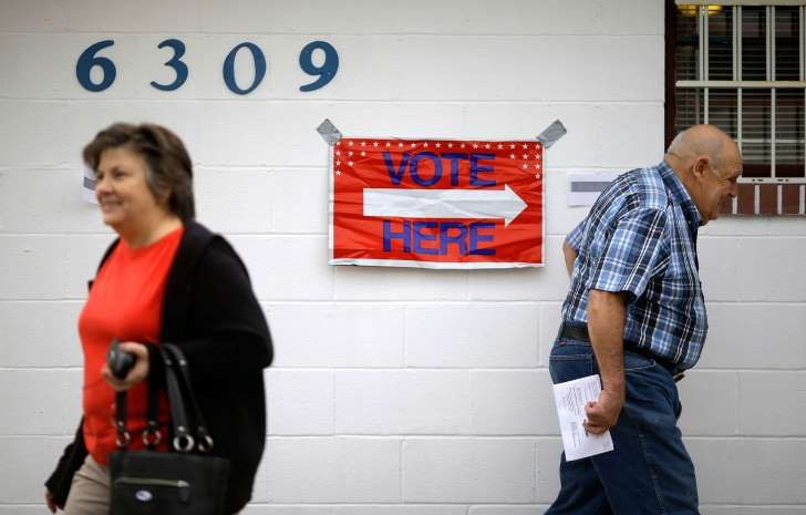 Voters enter and exit a polling place located inside the Veterans of Foreign Wars Gunpowder Post, Tuesday, Nov. 4, 2014, in Middle River, Md.