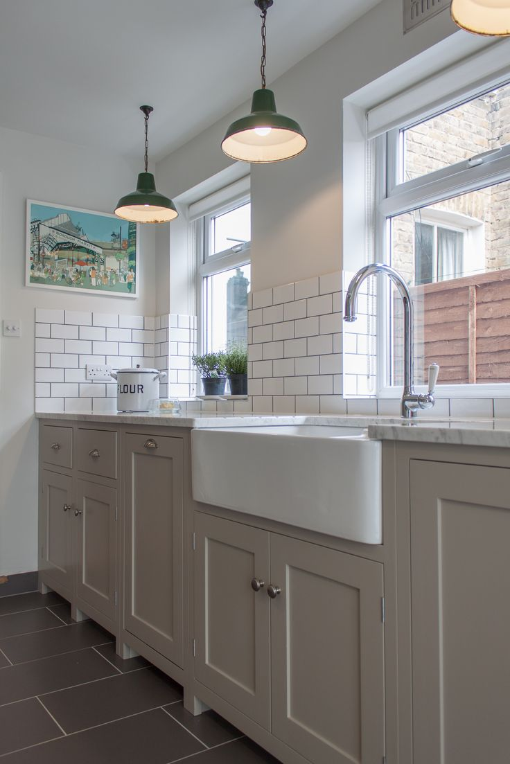 Wide belfast sink, putty units, white worktop. vintage pendant lighting