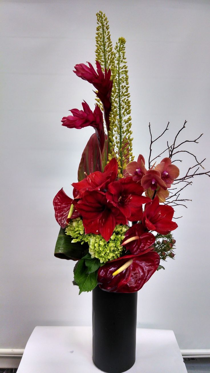 An arrangement we typically do for our offices. A formal linear with a slight garden look to it. The flowers in this arrangement are yellow eremerus (fox tall lilies), red amaryllis lilies, red gingers, red anthuriums, and a touch of #manzanita branches. Green hydrangeas are use to give contrast to this dramatic #tropical arrangement.