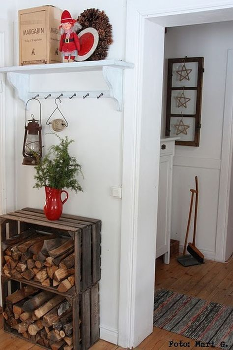 Wood crates are being used here to hold the firewood. They're placed on the entrance hallway, under the coat rack and they also serve as a side table.