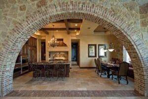 Diese Küche mit Mauerwerk Bogen dienen als Eingang Mittelmeer inspiriert ist. Es gibt Kronleuchter, eine Kochinsel und eine Ess-Set von Hölzern hergestellt. Die Decke ist elegant gestaltet, entsprechend den Ton von der Wand und die Böden. Schränke und dekorativen Malereien an der Wand hängen können auch notiert werden. Quelle: Zillow DigsTM