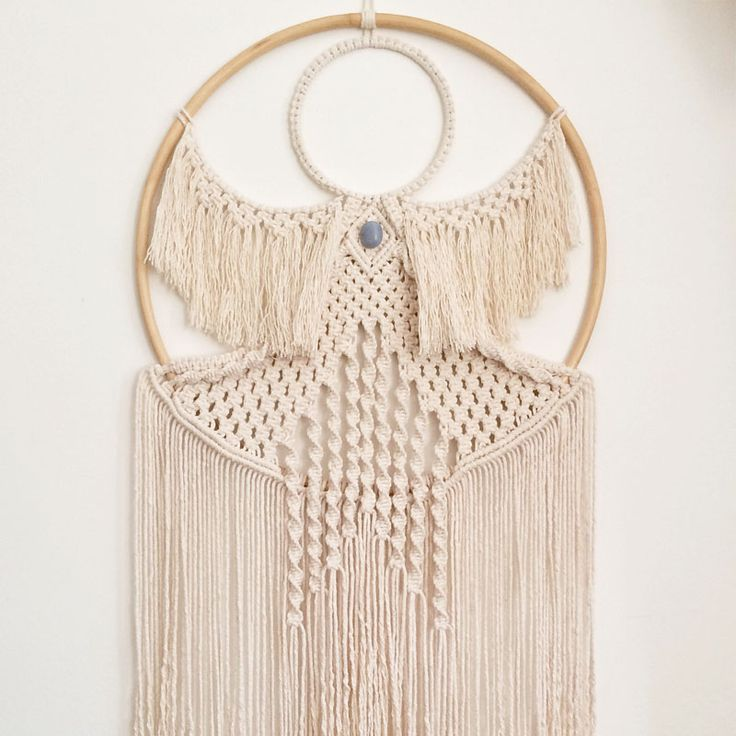 Angelic macrame wall hanging infused with an ANGELITE crystal. To not only adorn, but to act as a talisman. Buy now.