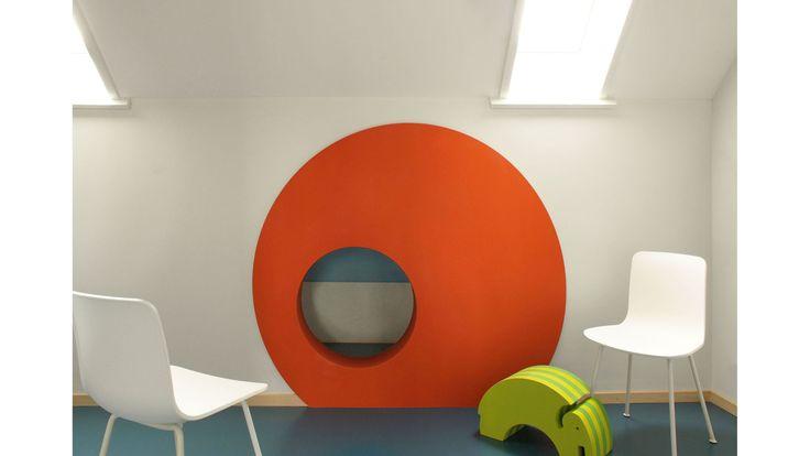 """Der Einbau der Kinderarztpraxis in einem Geschäftsbau wurde mit Holz und und Farben umgesetzt. Die """"Praxis bym Törli"""" erhielt eine wohnliche Atmosphäre."""