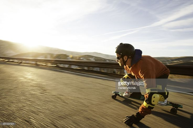 Lonboard skateboarder going down a road at sunset. (With