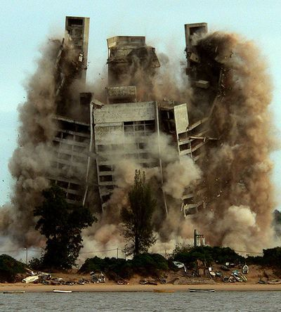 Brutalist building being destroyed by implosion.