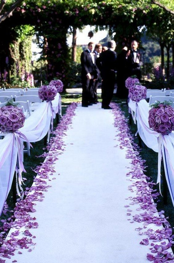 Pomanders of purple roses, scattered petals and purple satin ribbons line the aisle of this outdoor wedding ceremony