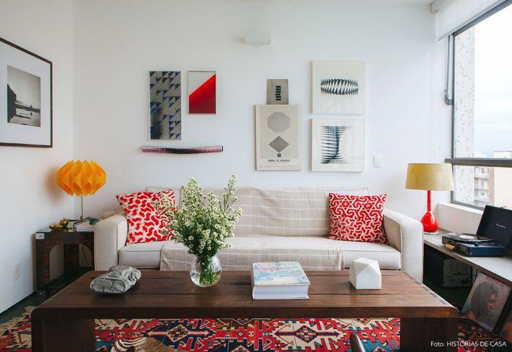 Sala de estar tem tapete kilim estampado e colorido, sofá bege e almofadas vermelhas.