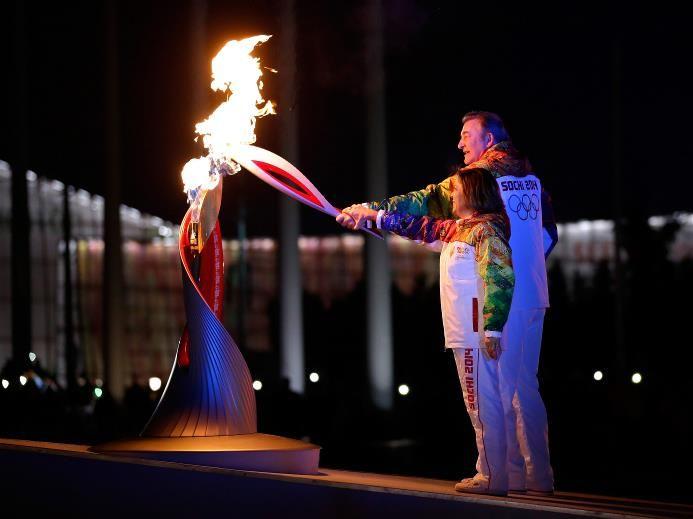 Irina Rodnina and Vladislav Tretyak light the Olympic cauldron during the opening ceremony