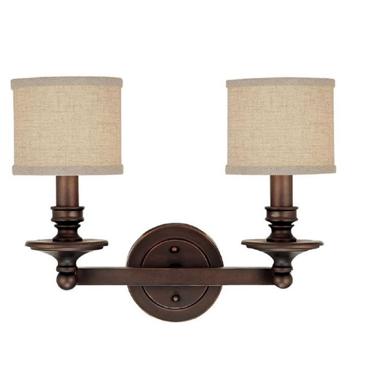 This Midtown collection 2-light bath/vanity light features a burnished bronze finish that will compliment many loft, urban and transitional decors. The beige decorative fabric shades soften the light and complete the look.