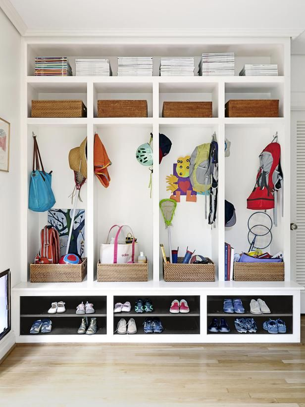 Sports equipment, coats, bags and magazine stacks stay organized in a wall of cubbies by the back door.