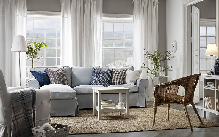 A light living room furnished with a light blue two-seat sofa with a chaise lounge filled with cushions. Shown together with a small white coffee table and a rattan armchair.