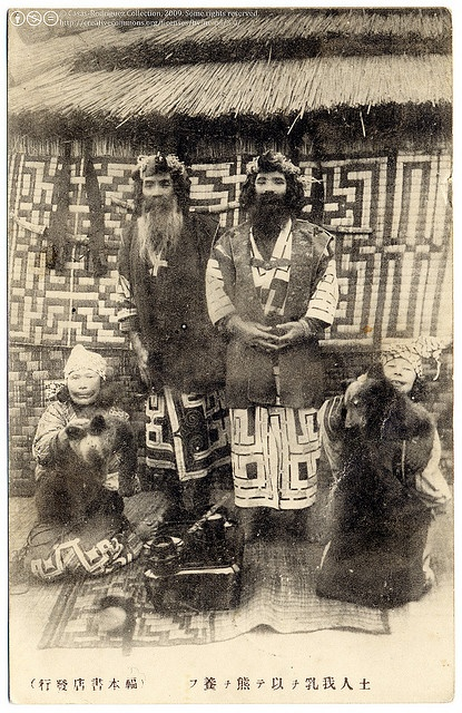 Two Ainu Men And Two Ainu Women Carrying Two Bears.  Japan.