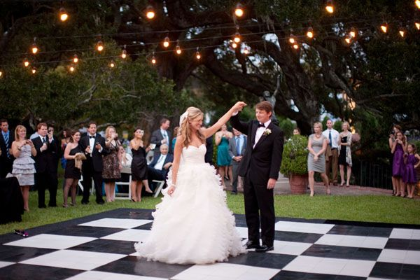 Reception Décor: A black and white dance floor transforms a backyard into an elegant, glamorous location for a wedding reception.