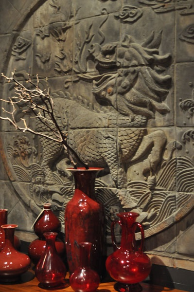 Terra Cotta tile depiction of a Chinese dragon, Chinese ox-blood ceramics in front.: