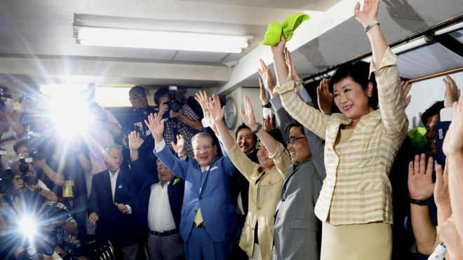 Yuriko Koike (right) and her supporters celebrate after exit polls predicted her election victory in Tokyo, Japan. July 31, 2016