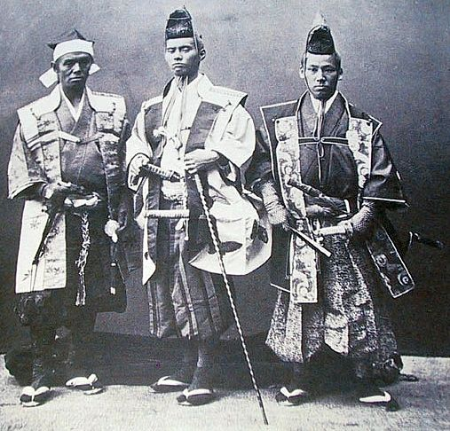 Three samurai, wearing jinbaori, the middle samurai is holding a muchi (whip).