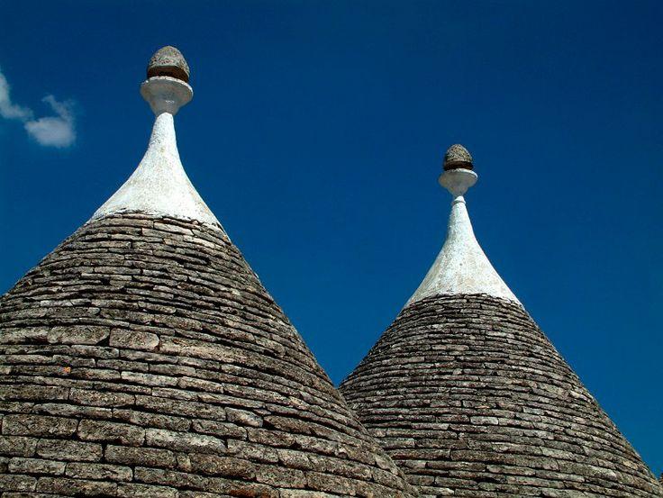 Alberobello, cuspidi bianche e grige di due trulli si stagliano contro il cielo.