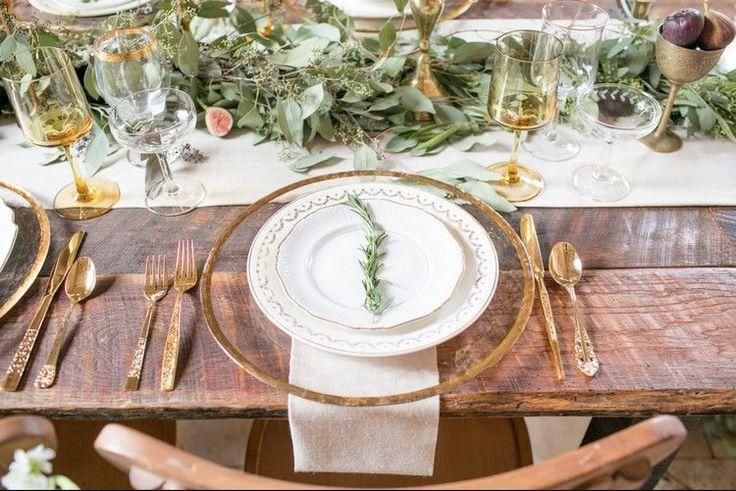 déco de table de style champêtre - des branches à feuilles vertes le long du chemin de table blanc, couverts de couleur or et vaisselle en blanc et or