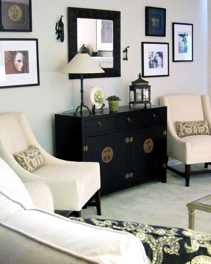 Chinese mandarin black chest anchors a black and white living room note the art wall as well find this pin and more on home decor