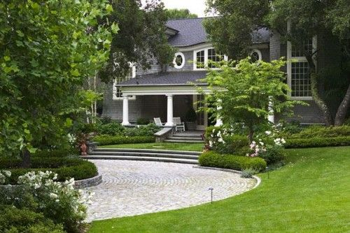 """Lawn sloping down onto the driveway makes the front feel enclosed and inside the natural setting; vs, """"over"""" & above it, ie separated off."""