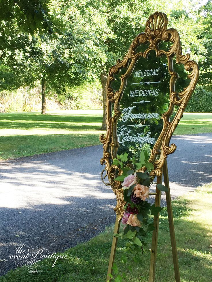 Our ornate gold mirror with white calligraphy on gold easel with a floral garland, in the trees at Harpers Homestead as the wedding welcome sign.