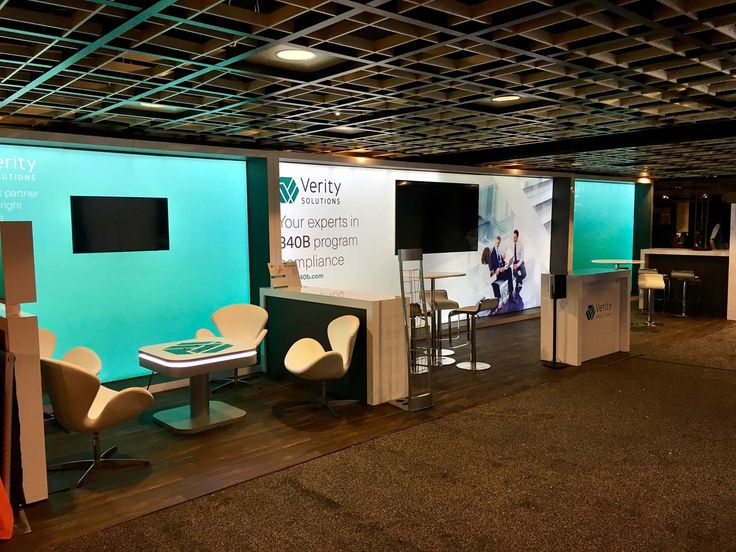 """Large Modular Inline LED Backlit Sague Exhibit Booth Wall. Features eco-friendly LED lighting, dye sublimation graphic printing on SEG recycled fabric, """"floating"""" LCD flat screen display monitors, modular locking trade show cabinets and custom event cell phone charging expo table! #backlitdisplays"""