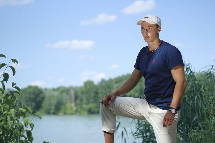 Yacht style men outfit photo next to beautiful river. As you can see, man wears Navy Explore T-Shirt by Pharos Apparel, white chinos and white cap.