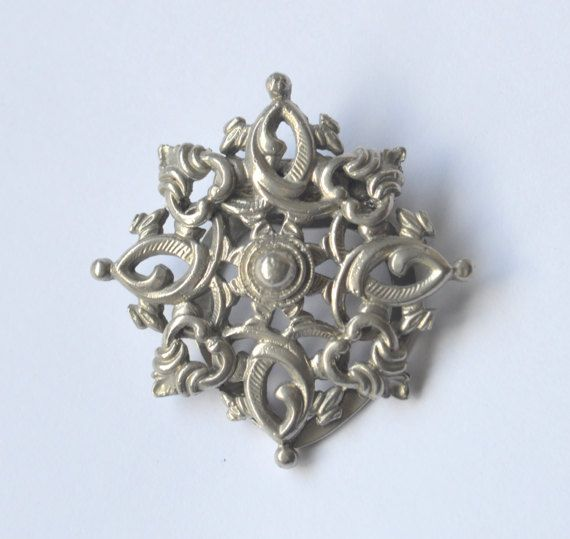 """A majestic Celtic style shield scarf ring/clip. It is in a shape of a knot with splendid ornamentation and made of silver tone metal. It measures 4.5 cm across (1.77). It has a hook for hanging a necklace chain or it can also be worn as a brooch. This clip is in a perfect vintage quality and it closes securely.  This Celtic style piece is inspired by the history and artwork of ancient Celtic cultures and can make a splendid addition to your smart outfit.  """"Fashion is what you're offered..."""